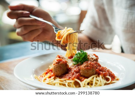 close up of woman eating spaghetti with fork  #299138780
