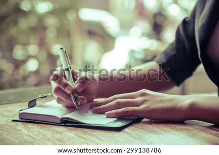 close up of woman writing her journal Royalty-Free Stock Photo #299138786