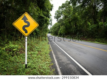 Curvy road sign to the mountain in rural area