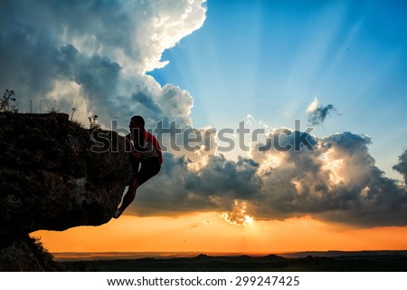 One guy climbing on a rock on sunset #299247425