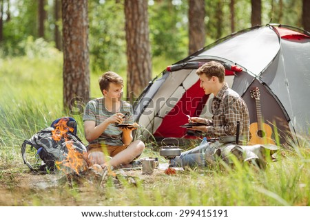Two young men are heated in a fire and cook out on a summer camp #299415191