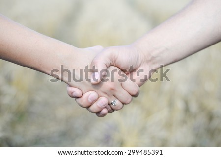 Male and female holding hands outdoors over bokeh background #299485391