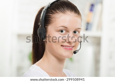 Pretty young smiling woman with a headset #299508941