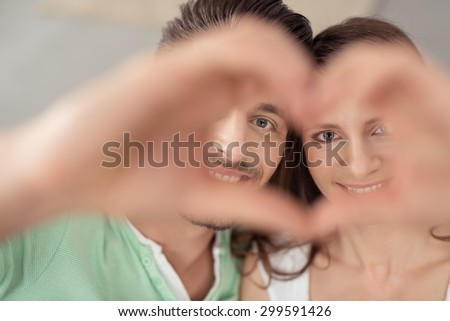 Close up Sweet Young Couple Looking at the Camera Through Hands Forming Heart Shape with Smiling Faces. #299591426