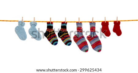 Four pairs of isolated handmade wool socks hanging on a rope. #299625434