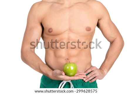 Man's abdominal muscles detail holding an apple isolated in white #299628575