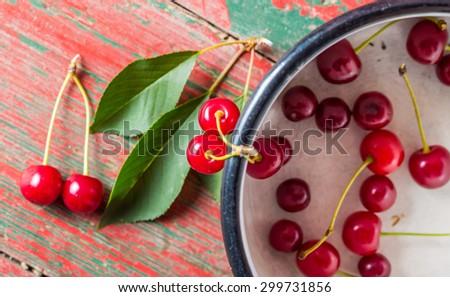 Fresh cherries in pot on old wooden table. studio shot #299731856