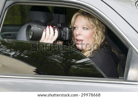 female private investigator or spy or secret agent taking photographs from car Royalty-Free Stock Photo #29978668