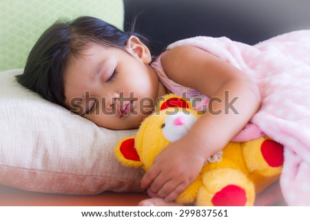 Adorable little girl sleeping in the bed with her toy #299837561