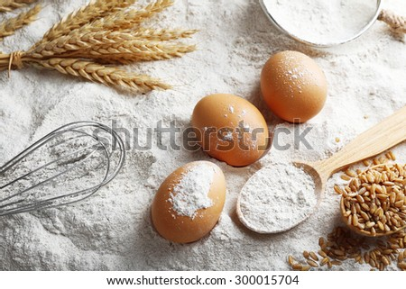 Wheat and eggs on white flour background #300015704