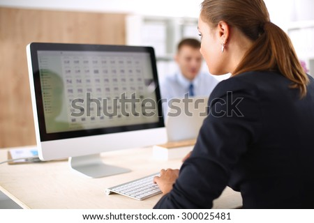 Young woman working in office, sitting at desk, using laptop #300025481