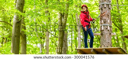 Teenager girl climbing in high rope course  #300041576
