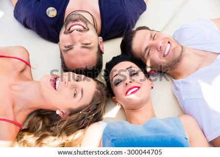 Friends lying in sand on beach, two women and two men #300044705