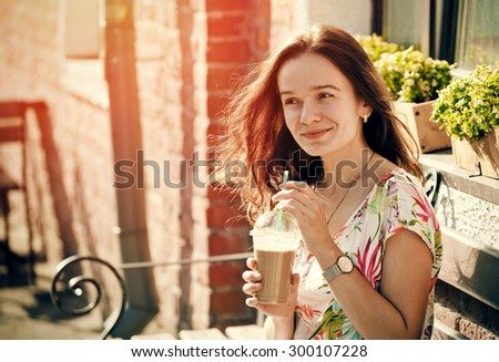 pretty smiling girl with milk shake sitting on bench at street cafe #300107228