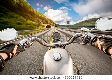 Biker driving a motorcycle rides along the asphalt road. First-person view. #300215792