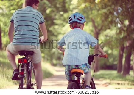 Happy father and son ride on bikes in summer park #300215816
