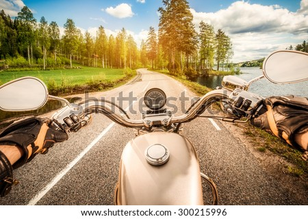 Biker driving a motorcycle rides along the asphalt road. First-person view. #300215996