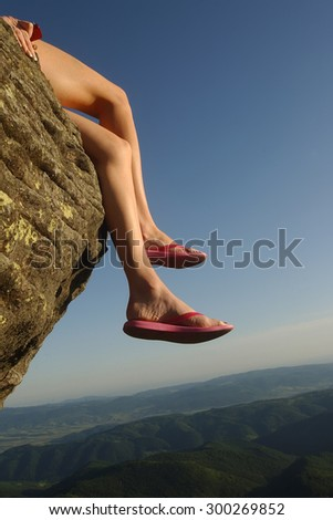 Beautiful view from high mountaing on green hills with forest and human female legs in slippers of woman sitting on rock on natural blue sky space background, vertical picture #300269852