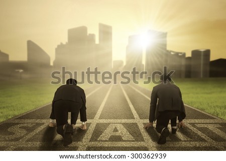Business competition: Rear view of two worker wearing formal suit and kneeling on the start line to compete Royalty-Free Stock Photo #300362939