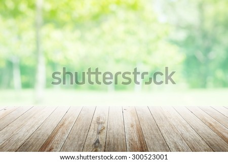 Empty wooden table with blurred city park on background