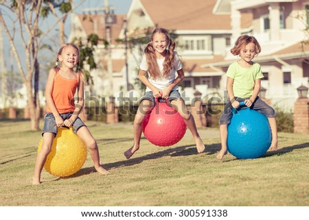 happy kids playing with inflatable balls on the lawn in front of house at the day time #300591338