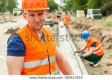 Construction worker in orange safety waistcoat and helmet #300617819