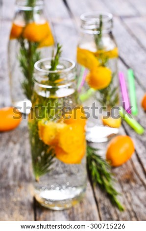 Blurred background: bottles with a clear liquid, citrus and rosemary on a wooden surface #300715226