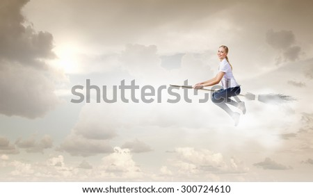 Happy young woman flying in sky on broom #300724610