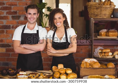 Portrait of smiling waiter and waitress with arms crossed at coffee shop #300759938