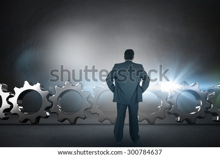 Businessman standing back to the camera with hands on hip against black wall #300784637