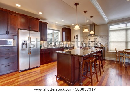 State of the art kitchen with deep stained cabinets, and stainless steel fridge. #300837317