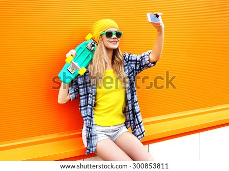 Fashion and technology concept - stylish young girl in colorful clothes with skateboard having fun makes self-portrait on the smartphone against the orange wall