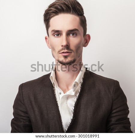 Elegant young handsome man in long stylish coat. Studio fashion portrait.  #301018991