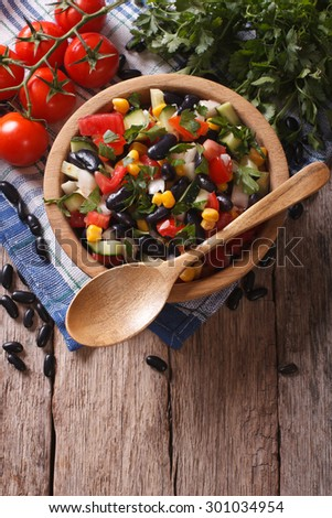 Mexican vegetable salad with black beans in a wooden bowl, close-up and ingredients on the table. vertical top view #301034954