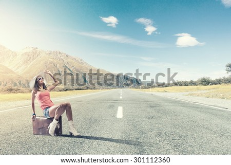 Traveler woman sits on retro suitcase and waiting for car #301112360