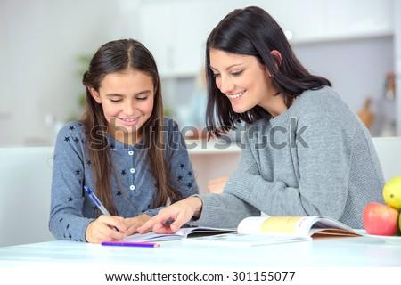 Mom helping her daughter do her homework #301155077