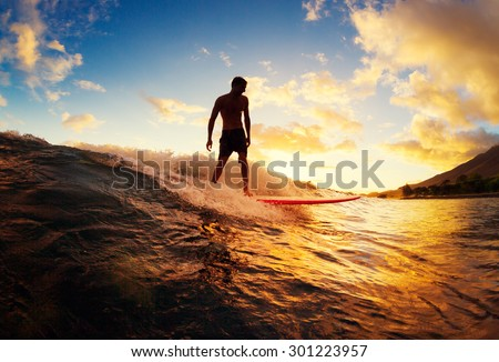 Surfing at Sunset. Young Man Riding Wave at Sunset. Outdoor Active Lifestyle. Royalty-Free Stock Photo #301223957