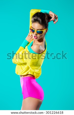 Expressive fashion model posing in vivid colourful clothes. Bright fashion. Optics, eyewear. Studio shot. #301226618