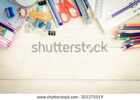 School and office supplies on wood background.