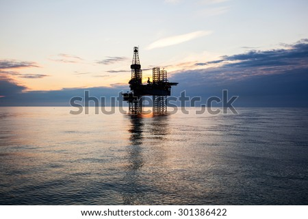 Silhouette of oil rig at sunset Royalty-Free Stock Photo #301386422