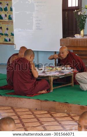 KYAUKME, MYANMAR - FEB 21, 2015 - Buddhist monks eating their main meal of the day at noon, Kyaukme Myanmar (Burma) #301566071