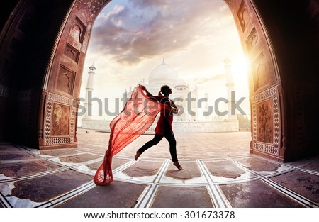 Woman with red scarf dancing near Taj Mahal in Agra, Uttar Pradesh, India Royalty-Free Stock Photo #301673378