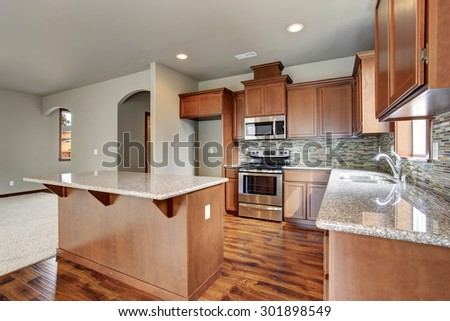 New 2015 American middle class kitchen. Cherry wood color of cabinets and laminate flooring.  #301898549