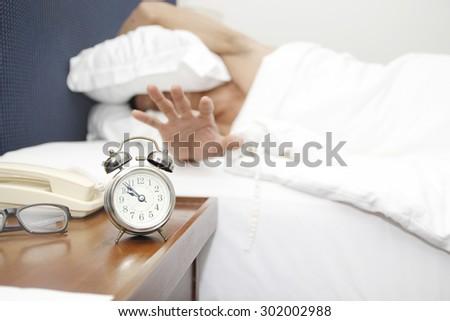 sleeping man disturbed by alarm clock #302002988