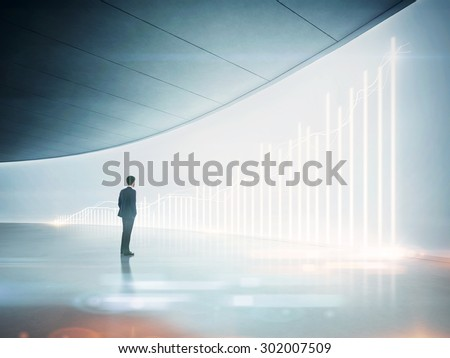 Businessman looking at shining chart on the wall
