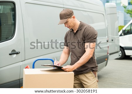 Young Happy Delivery Man With Cardboard Boxes Writing On Clipboard #302058191
