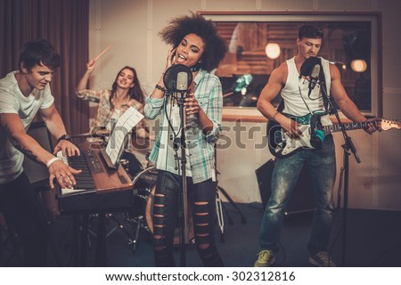 Multiracial music band performing in a recording studio  Royalty-Free Stock Photo #302312816