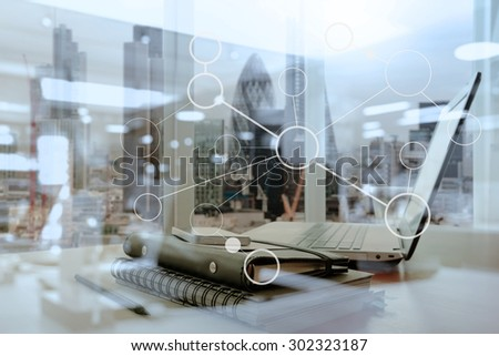 Office workplace with laptop and smart phone on wood table and london city blurred background Royalty-Free Stock Photo #302323187