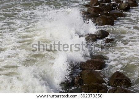 tidal bore: waves with foam and  granite stones #302373350