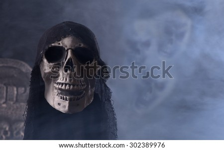 Halloween grim reaper head with scary faces in a background of swirling smoke #302389976